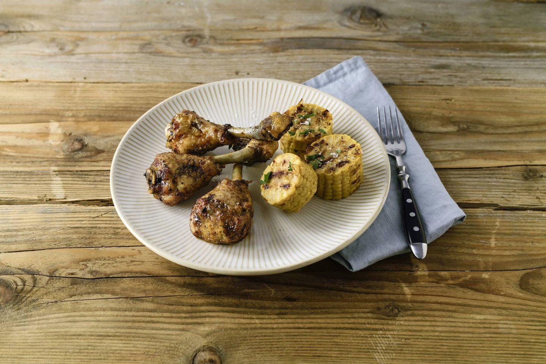 Grill-Gefluegel Chickendrumsticks mit Maiskolben