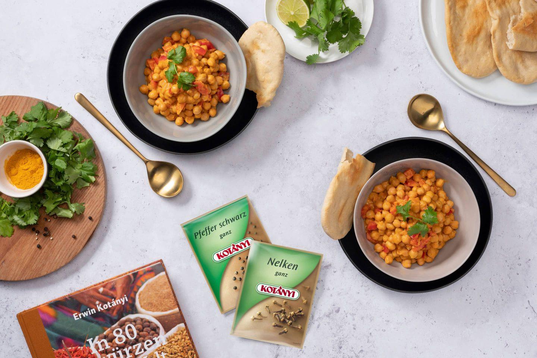 Slanutak u curry umaku s naanom uz vrećice crnog papra i cijelog klinčića.