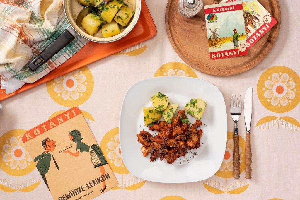 Svinjetina začinjena kimom poslužena na pravokutnom tanjuru uz krumpir s peršinom.