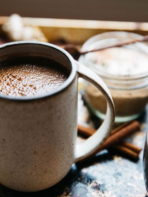 A cup of coffee with cinnamon sticks on a table.