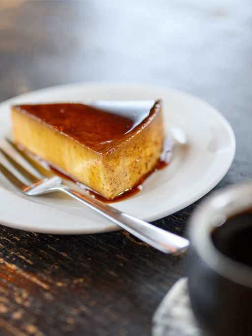 A piece of caramel cake on a white plate.