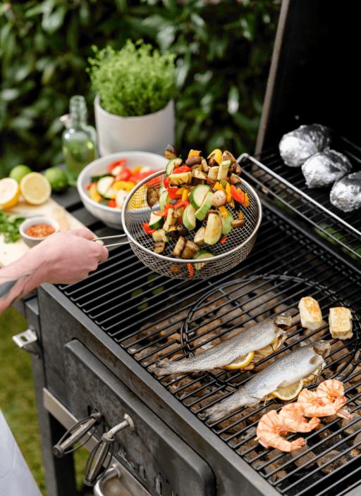 Košara za prženje s pečenim povrćem i pastrvom s limunom pečenom na roštilju.